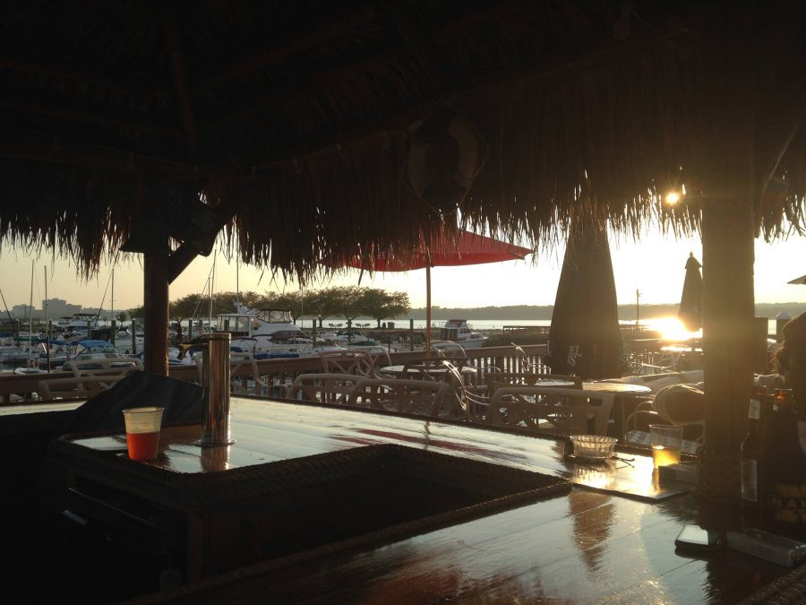 A shot of a sunset at a patio overlooking a waterfront at a restaurant.