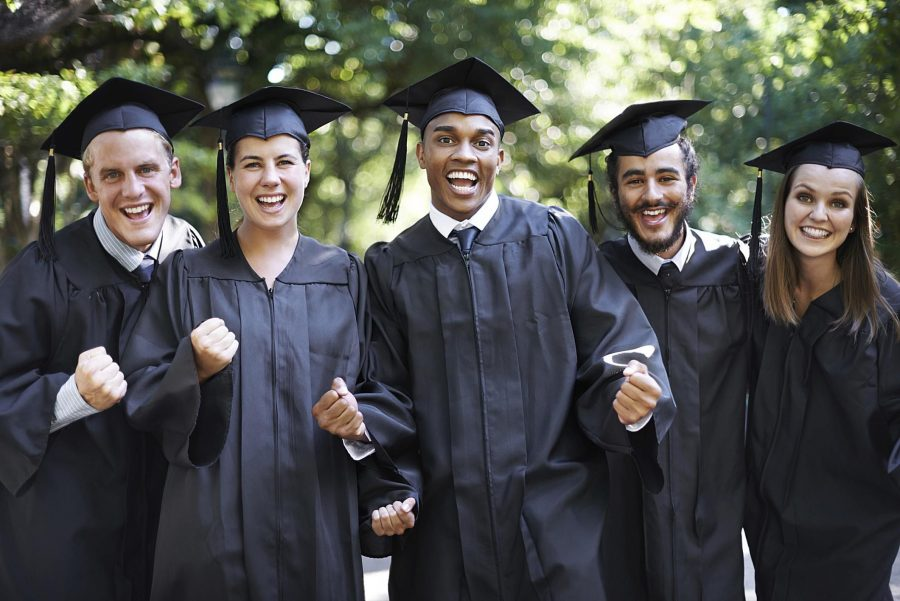 A group of college graduates in cap and gowns smile at the camera.
