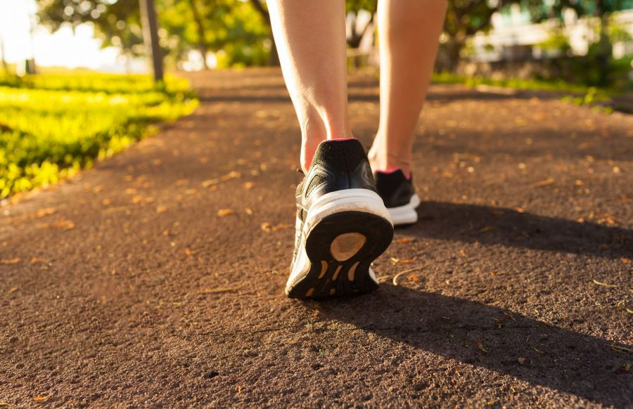 A closeup of a woman's legs with workout sneakers on pavement.